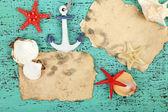 Decoração de conchas, estrelas do mar e papel velho na cor de fundo de madeira — Fotografia Stock