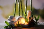 Spa composition with herbal massage bags, candle and bamboo on table on natural background — Stock Photo