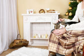 Woman and cute cat sitting on rocking chair in the front of the fireplace — Stock Photo