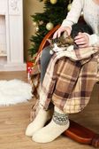 Woman and cute cat sitting on rocking chair in the front of the Christmas tree — Стоковое фото