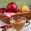 Apple cider with cinnamon sticks and fresh apples in wicker basket on wooden table, on bright background — Stock Photo #55326315