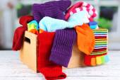 Multicoloured socks in a box on a wooden table in front of the window — Stock Photo