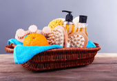 Shower kit in a brown rectangular basket on wooden table — Stock Photo