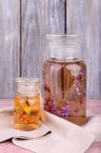 Bottles of herbal tincture on a wooden table in front of wooden wall — Stock Photo