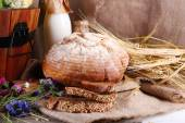 Big wooden basket, ears bread, dried flowers and milk on sacking background — Stock Photo