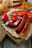 Smoked thin sausages and vegetables on cutting board, on wooden background — Stock Photo