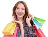 Schöne junge frau mit einkaufstüten, die isoliert auf weiss — Stockfoto