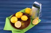 Lemons on plate and grater on green napkin on dark blue wooden background — Stock Photo