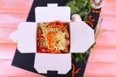 Paket servisi olan restoran kutusunda pembe bir arka plan üzerinde siyah mat Çin eriştesi — Stok fotoğraf