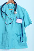 Doctor shirt with stethoscope on hanger on blue background — 图库照片