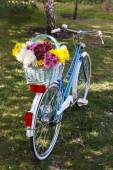 Bicycle with flowers in metal basket — Stock Photo