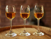 Glasses of wine in cellar with old barrels  — Stock Photo