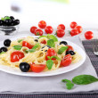 Spaghetti with tomatoes, olives and basil leaves on plate on napkin on fabric background — Stock Photo #55349407