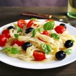 Spaghetti with tomatoes, olives and basil leaves on plate on wooden background — Stock Photo #55349411