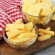 Raw peeled and sliced potatoes in glass bowls, on cutting board, on color wooden background — Stock Photo #55349591