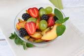 Fresh tasty fruit salad on wooden table — Stock Photo