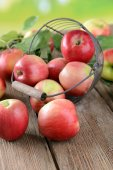 Sweet apples in wicker basket on table on bright background — Stock Photo