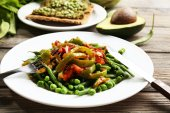 Healthy salad with peas and asparagus served on wooden table, close-up — Stock Photo