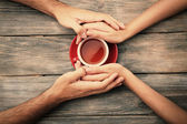 Tea cups and holding hands at the wooden table — Stock Photo