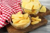 Raw peeled and sliced potatoes in glass bowls, on cutting board,  on color wooden background — Stock Photo