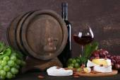 Supper consisting of Camembert cheese, wine and grapes on cutting board and wine barrel on wooden table on brown background — Stock Photo