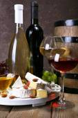 Supper consisting of Camembert cheese, honey, wine and grapes on stand and wine barrel on wooden table on brown background — Stock Photo