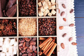 Wooden box with set of coffee and cocoa beans, sugar cubes, dark chocolate, cinnamon and anise on wooden background — Stok fotoğraf