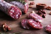 French salami and walnuts on wooden background — Stock Photo