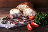 French salami with tomatoes, parsley and bread on cutting board on wooden background — Stock Photo