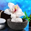 Spa composition with candle and white orchid on table on blue background — Stock Photo #55350689