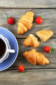 Breakfast with tea and fresh croissants on wooden background — Stock Photo
