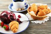 Breakfast with tea, raspberry jam and fresh croissants on wooden background — Stock Photo