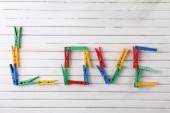 Love word formed with colorful clothespins on wooden background — Stockfoto