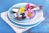 Plates and vintage cutlery on color wooden background — Zdjęcie stockowe