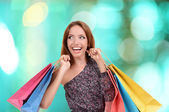Shopping concept. Beautiful young woman with shopping bags on bright background — Foto de Stock
