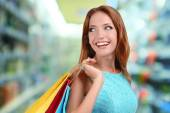 Shopping concept. Beautiful young woman with shopping bags on shop background — Foto de Stock