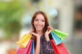 Shopping concept. Beautiful young woman with shopping bags on bright background — Stock Photo