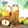 Apple cider vinegar in glass bottle and ripe fresh apples, on wooden table, on nature background — Stock Photo #55570405