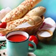 Homemade tomato juice in color mug, bread sticks, spices and fresh tomatoes on wooden table, on bright — Stock Photo #55635717