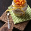 Healthy breakfast - yogurt with fresh peach and muesli served in glass jar, on wooden background — Stock Photo #55636043