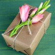 Natural style handcrafted gift box with fresh flowers and rustic twine, on wooden background — Stock Photo #55638305