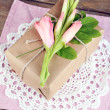 Natural style handcrafted gift box with fresh flowers and rustic twine, on wooden background — Stock Photo #55638307