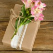 Natural style handcrafted gift box with fresh flowers and rustic twine, on wooden background — Stock Photo #55638309