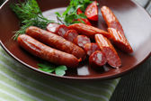Assortment of tasty thin sausages on plate on wooden background — Stock Photo