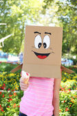 Woman with cardboard box on her head with happy face holding ice cream, outdoors — Stock Photo