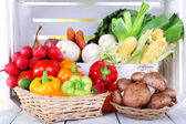 Vegetables in crate and in baskets on white wooden box background — Stock Photo