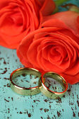 Wedding rings on wedding bouquet, close-up, on color wooden background — Stock Photo