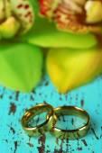 結婚指輪と蘭の花、木の背景の色にクローズ アップ — ストック写真