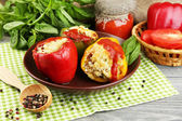 Composition with prepared stuffed peppers on plate and fresh herbs, spices and vegetables, on wooden background — Stock Photo