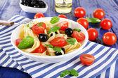 Peçete ahşap zemin üzerinde plaka üzerinde spagetti domates, zeytin ve fesleğen yaprakları — Stok fotoğraf